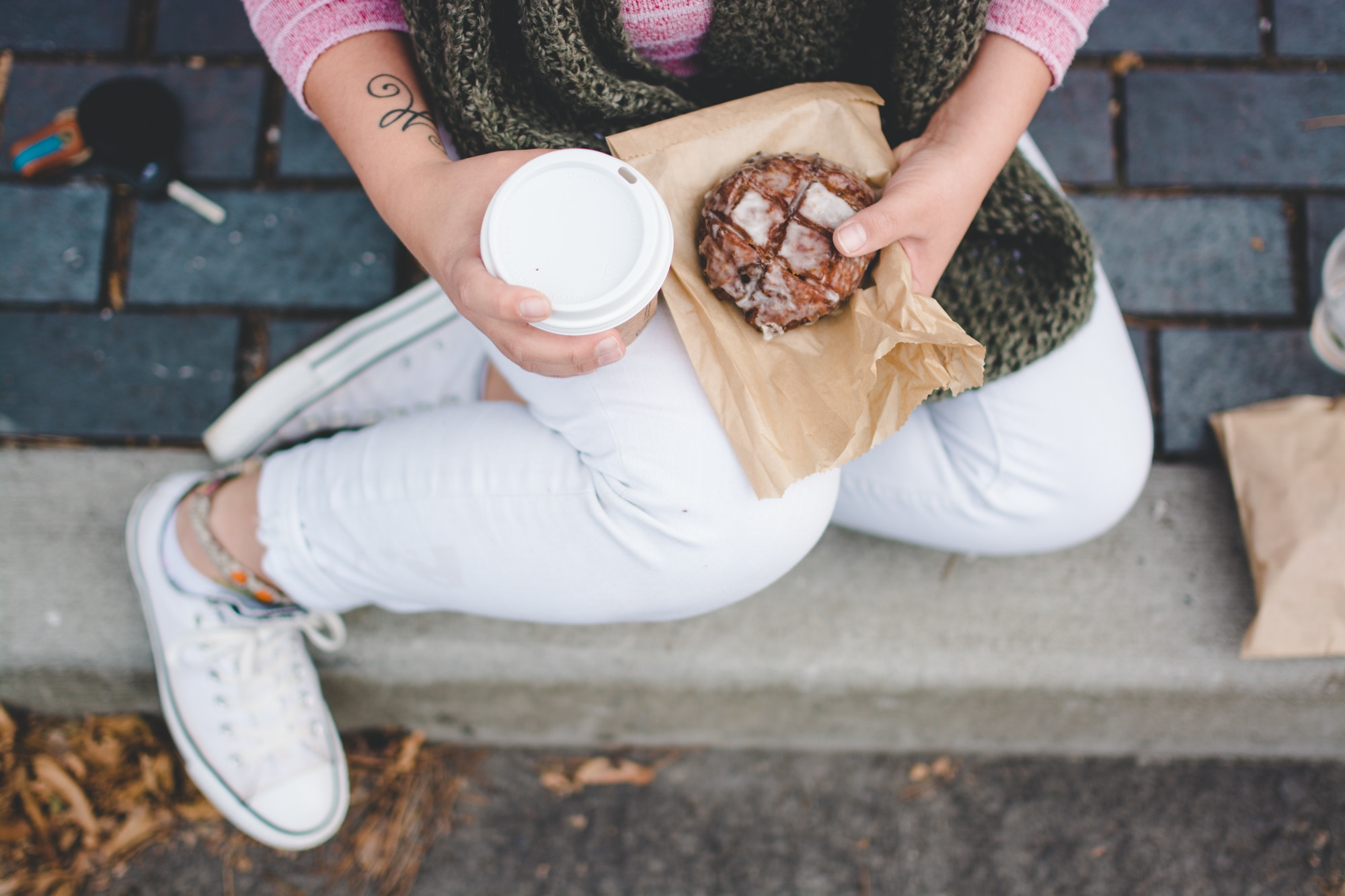 Woman holding coffee and pastry